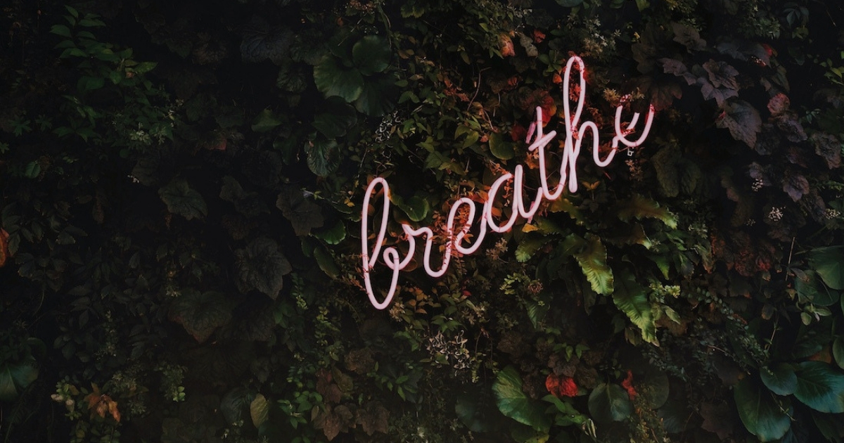 "Neon white sign that says ""breathe"""