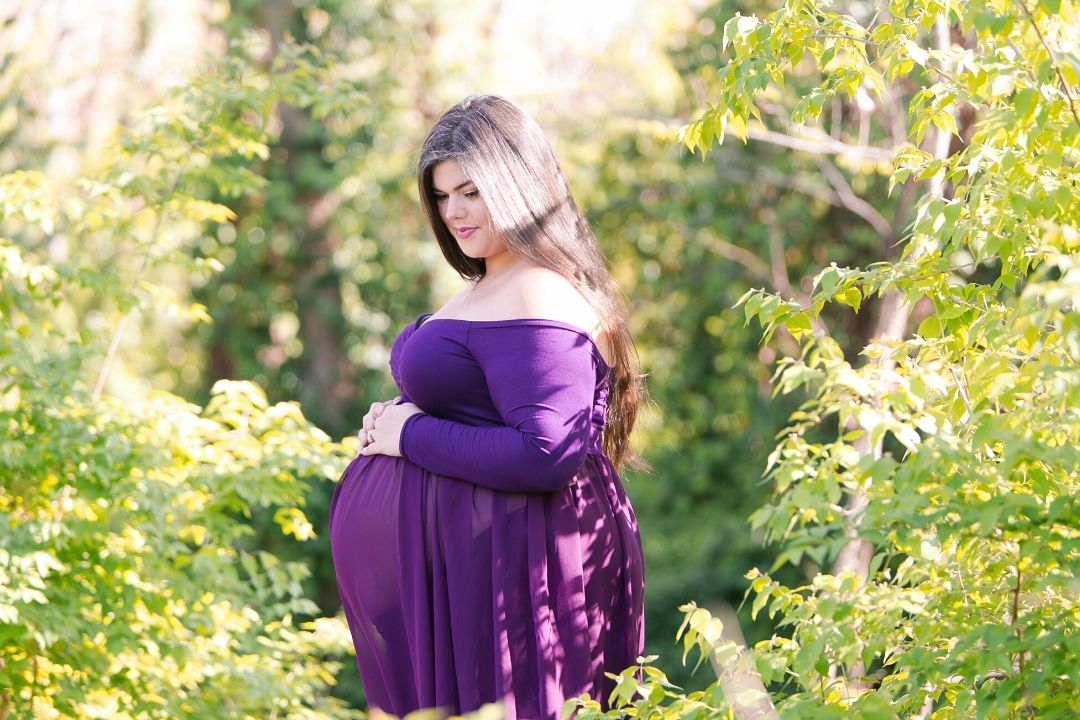 Plus Size Pregnancy With Twins woman wearing plus size purple gown