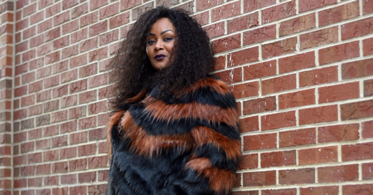 plus size woman in faux fur jacket leaning against brick wall