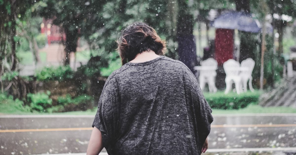 plus size woman walking in the rain