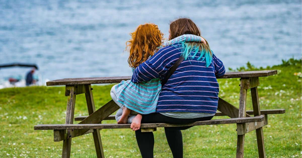 plus size mother with daughter sitting on a bench
