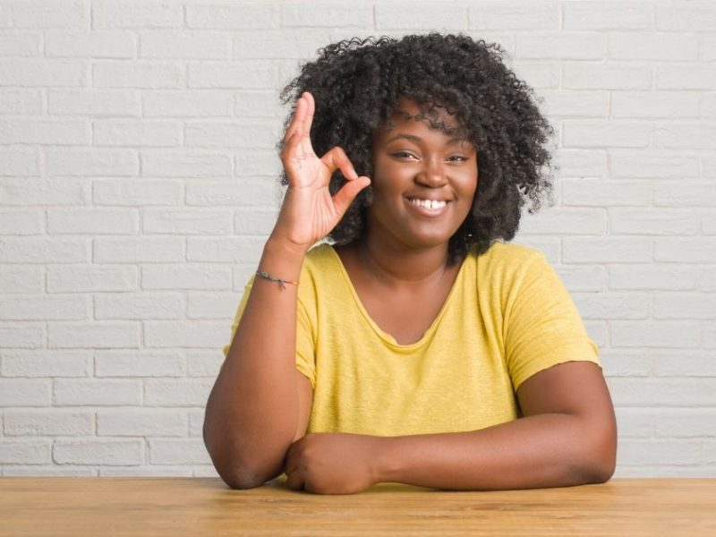 plus size woman holding up fingers to say okay for new year same you