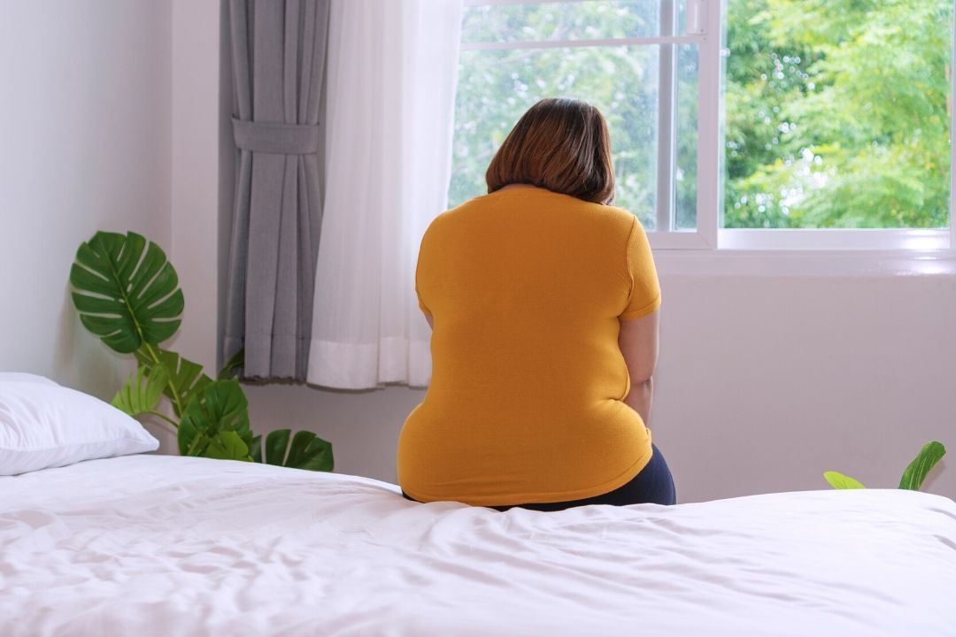 a woman sitting on her bed with Vaginismus