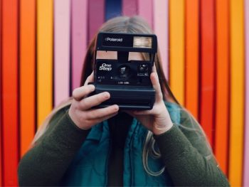 woman holding camera with colorful background