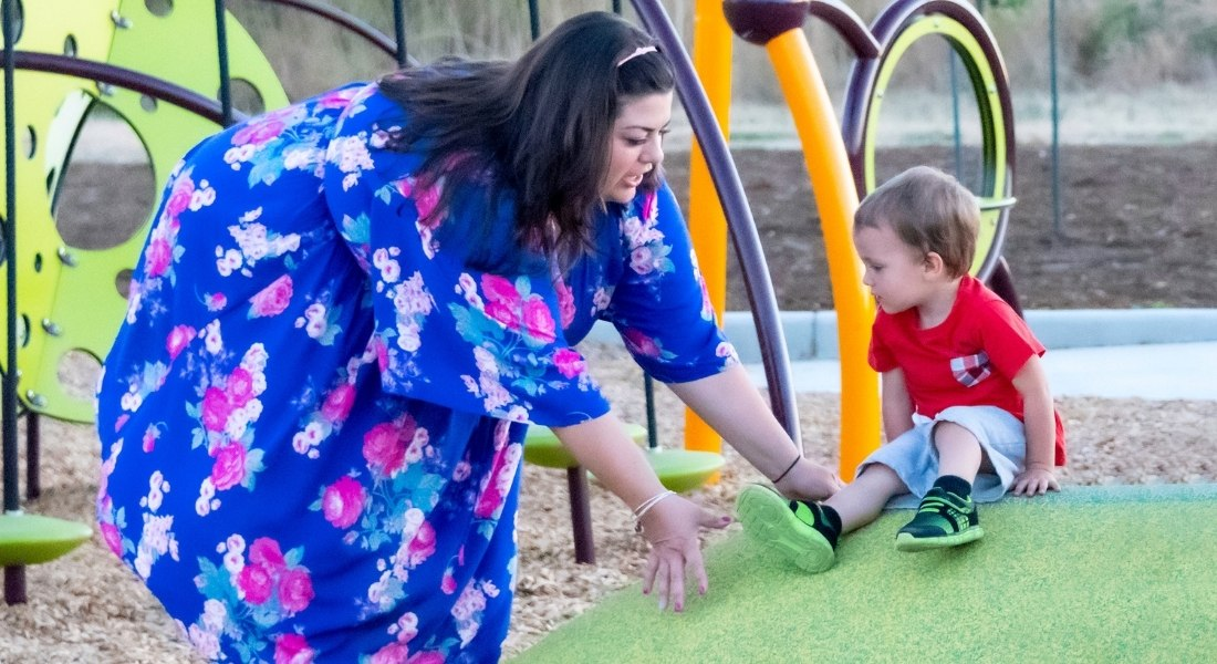 plus size mom helping son on playground